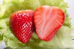 2 половины клубники на зеленом салате листают Стоковая Фотография RF