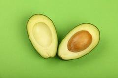 2 половины свежего авокадоа отрезка на зеленой книге Стоковое Изображение