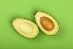 2 половины свежего авокадоа отрезка на зеленой книге Стоковые Изображения RF