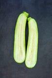 2 половины свежего зеленого цукини изолированного на сером шифере Стоковая Фотография