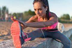 Подогрев девушки спортсмена фитнеса модельный протягивая ее подколенные сухожилия, ногу и назад Молодая женщина работая с наушник Стоковые Фото