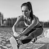 Подогрев девушки спортсмена фитнеса модельный протягивая ее подколенные сухожилия, ногу и назад Молодая женщина работая с наушник Стоковая Фотография RF