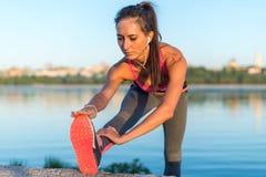 Подогрев девушки спортсмена фитнеса модельный протягивая ее подколенные сухожилия, ногу и назад Молодая женщина работая с наушник Стоковое фото RF