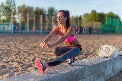 Подогрев девушки спортсмена фитнеса модельный протягивая ее подколенные сухожилия, ногу и назад Молодая женщина работая с наушник Стоковая Фотография