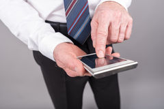 Положение бизнесмена, используя его smartphone стоковое фото rf