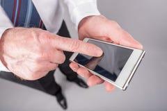 Положение бизнесмена, используя его smartphone стоковое изображение rf