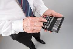 Положение бизнесмена, используя калькулятор стоковые изображения