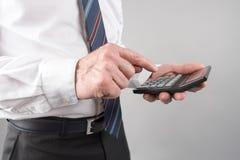 Положение бизнесмена, используя калькулятор Стоковое фото RF