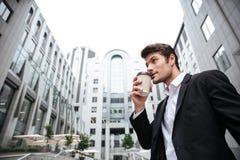 Положение бизнесмена и выпивая кофе взятия отсутствующий около делового центра Стоковые Изображения RF