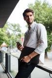 Положение бизнесмена и использовать сотовый телефон outdoors Стоковое фото RF