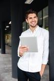 Положение бизнесмена и использовать таблетка outdoors Стоковые Изображения