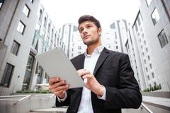 Положение бизнесмена и таблетка использования около делового центра Стоковое Фото