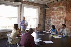 Положение бизнесмена для того чтобы адресовать встречу зала заседаний правления Стоковое фото RF