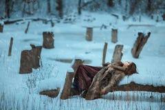 Положение девушки на дереве и замораживании в зиме Стоковые Изображения RF