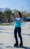 Положение девушки ролика и selfie стрельбы на smartphone Стоковое Изображение