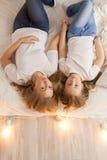 Положение матери и дочери на кровати и взгляд на камере над взглядом единение просторная квартира конструкции нутряная самомодней Стоковое Изображение RF