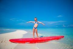 Положение маленькой прелестной практики девушки занимаясь серфингом на Стоковые Фотографии RF