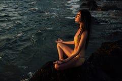 Положение лотоса девушки раздумья на камне на предпосылке сногсшибательного моря Стоковая Фотография
