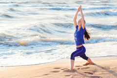 Положение ратника йоги женщины практикуя на пляже Стоковое фото RF