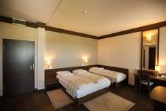 положите белизну в постель стены подушки nightstand светильника части спальни роскошную стоковые фото