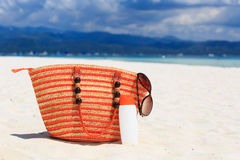 Положите в мешки, стекла солнца и suncream на тропическом пляже Стоковое Фото