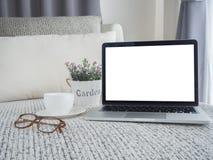 Положите в постель с пустым экраном на компьтер-книжке, белой керамической белой кофейной чашке, Стоковое фото RF