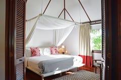 Положите комнату в постель современной деревянной гостиницы дома в тропической стране Стоковое фото RF