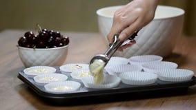 Положите тесто в бумажные стаканчики Тесто торта руки лить в поднос булочки сток-видео