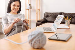 Положительная азиатская женщина вязать в офисе Стоковая Фотография