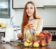 Положительная девушка варя напитки от персиков Стоковая Фотография