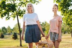 Положительная девушка и ее бабушка нося корзину пикника Стоковые Изображения