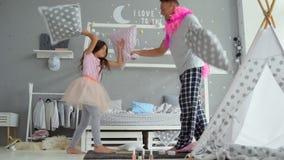 Положительная девушка и ее отец воюя с подушками сток-видео