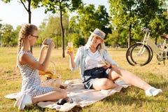 Положительная девушка teener принимая фото ее бабушки на пикнике Стоковое Изображение RF
