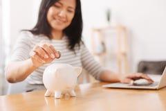 Положительная женщина кладя монетки в копилку Стоковое фото RF