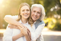 Положительная женщина наслаждаясь прогулкой с пожилым родителем на улице стоковые фотографии rf