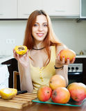 Положительная женщина с зрелым манго в доме Стоковое фото RF