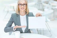 Положительная коммерсантка держа лист бумаги Стоковая Фотография