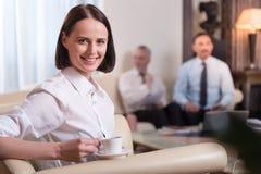 Положительная красивая женщина сидя на кресле Стоковые Изображения
