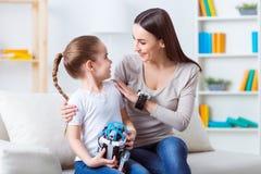 Положительная мать и ее дочь сидя на софе Стоковая Фотография