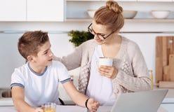 Положительная мать и мальчик отдыхая в кухне Стоковое Изображение RF