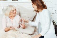 Положительная медсестра навещая больная женщина дома Стоковые Изображения RF
