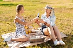 Положительная милая девушка подростка отдыхая в парке с ее бабушкой Стоковое фото RF