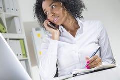 Положительная молодая африканская женщина в офисе стоковая фотография