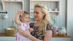 Положительная молодая мать держа ее младенца в кухне дома сток-видео