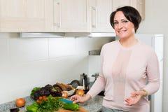 Положительная домохозяйка варя veggies дома Стоковое фото RF