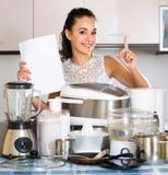 Положительная домохозяйка с бумагой и multicooker Стоковое Фото