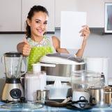 Положительная домохозяйка с приборами в отечественной кухне Стоковые Изображения