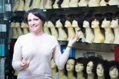 Положительная середина постарела женский клиент выбирая естественный парик волос Стоковые Фотографии RF