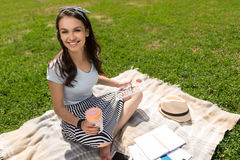 Положительная усмехаясь женщина отдыхая на траве Стоковые Фотографии RF