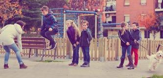 Положительные дети играя в игре веревочки скачки Стоковые Фото